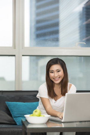 Young Chinese woman at home relaxing in her lounge and using a laptop Stock Photo - 22505409