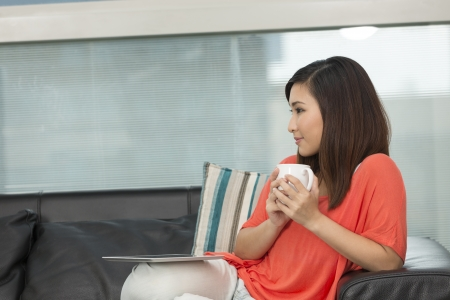 Young Chinese woman sitting at home on sofa relaxing. Beautiful Asian woman at relaxing home. photo