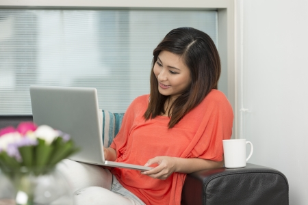 Young Chinese woman at home relaxing in her lounge and using a laptop photo