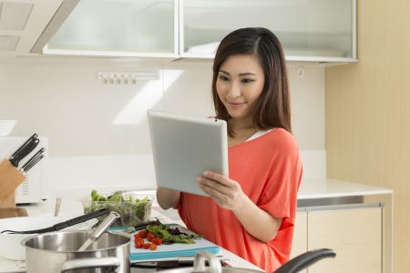 Asian woman in kitchen reading a recipe from a digital tablet. Young chinese woman in her twenties preparing food. photo