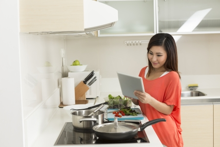 Asian woman in kitchen reading a recipe from a digital tablet. Young chinese woman in her twenties preparing food. Stock Photo