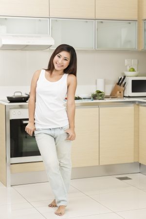 Happy Chinese woman standing at home in her kitchen Stock Photo - 22505458