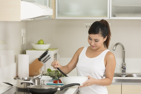 Asian woman in kitchen making food for dinner. Young chinese woman in her twenties preparing food. photo
