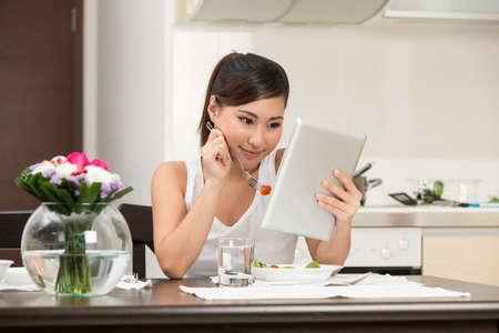 tabla de surf: Mujer china joven que come y que lee una tableta digital.