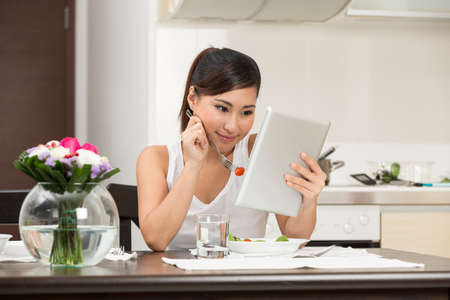 Young Chinese woman eating and reading a digital tablet. photo
