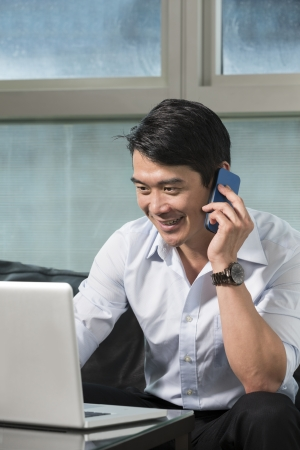 Chinese business man talking on a mobile phone and working on his laptop Stock Photo - 22674002
