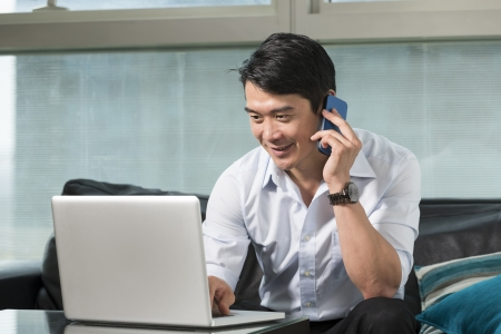 house call: Chinese business man talking on a mobile phone and working on his laptop