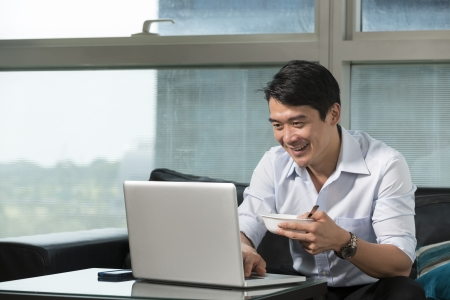 Chinese business man having breakfast and working his laptop. photo