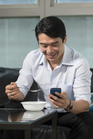Chinese Business man having breakfast and checking his phone. photo