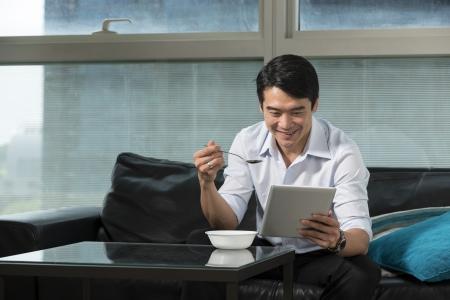 L'homme d'affaires chinois manger le petit déjeuner à la maison et lire sa tablette PC. Banque d'images