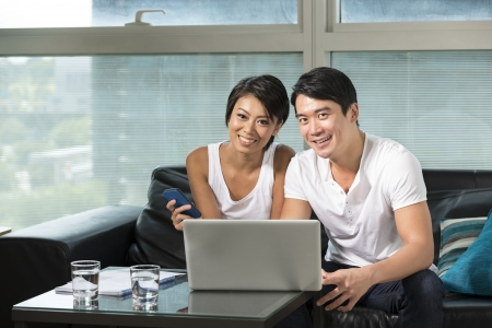 Chinese couple relaxing at home with a laptop on a sofa in their living room photo