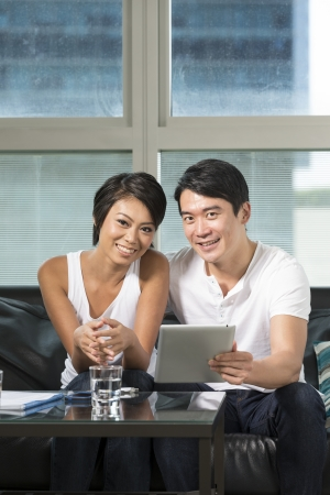 Chinese couple relaxing with a digital tablet in their living room photo