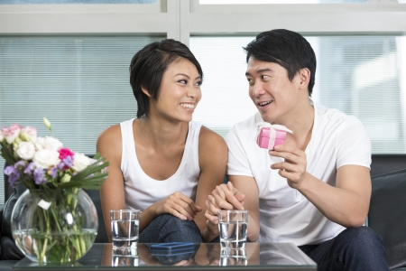 Happy Chinese man giving a present to his girlfriend at home in their living room photo