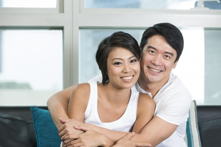 Yound and happy Chinese couple posing together at home
