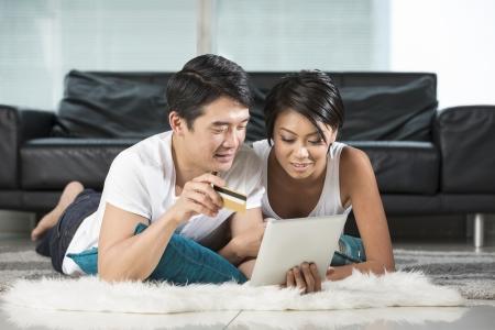 Portrait d'un couple chinois heureux couchée sur le plancher de salon et shopping en ligne