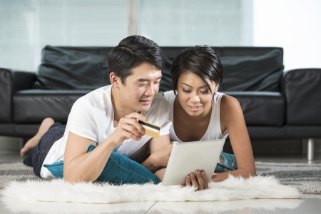 Portrait of a happy Chinese couple lying on lounge floor and Shopping Online
