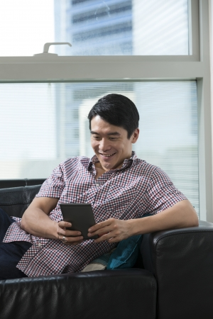 Happy Chinese man at home on sofa using a digital Tablet PC. photo