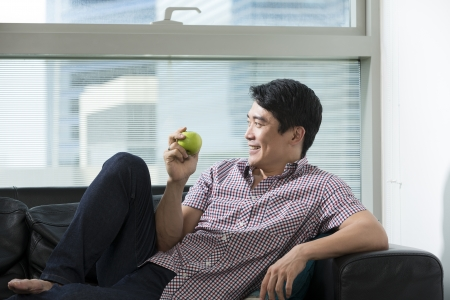 chinese adult: Healthy Chinese man eating an apple while relaxing at home. Healthy eating concept.