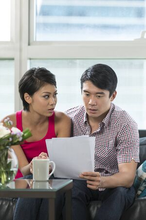 Serious Chinese couple reading a financial bill or document at home photo