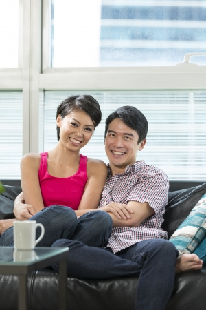Young and happy Chinese couple hanging out together at home photo
