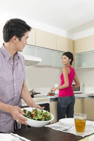 Happy young Chinese couple preparing to eating dinner at home in the kitchen photo