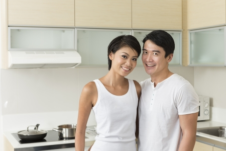 Young Chinese couple posing in the kitchen at home photo