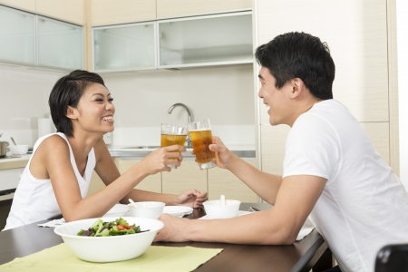 Happy young Chinese couple eating at home in the kitchen