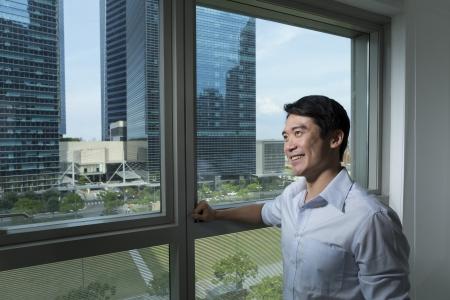out think: Feliz el hombre de negocios chino que mira fuera de una ventana de la oficina.