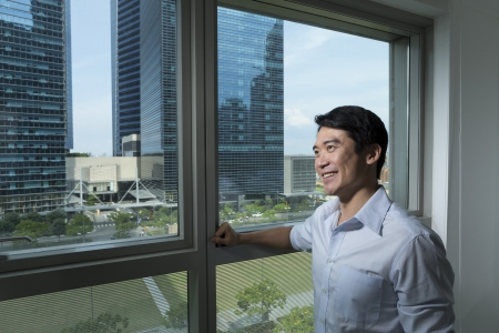 looking out: Happy Chinese business man looking out of an office window. Stock Photo