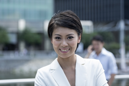 Portrait of a confident Chinese businesswoman standing outside in business district. photo