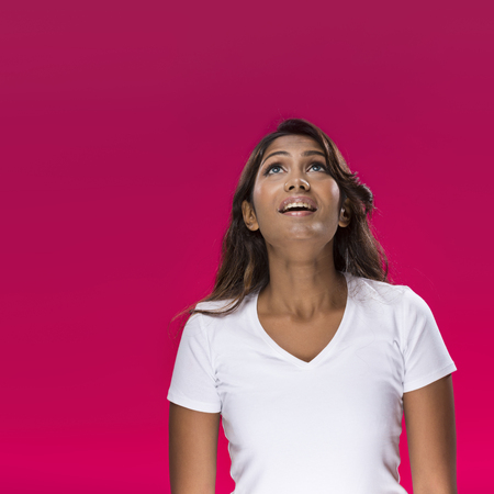looking upwards: Portrait of happy Indian Woman looking upwards on bright pink background.  Stock Photo