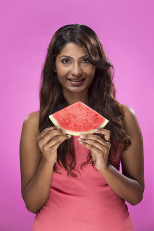 Happy Indian Woman holding a slice of watermelon on colorful background. Healthy eating concept. Young and fresh Asian female model on pink background. photo