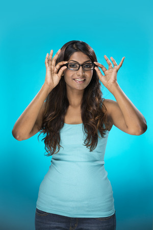 spectacle: Portrait of stylish Indian Woman wearing glasses. Young fresh Indian female model on bright blue background.