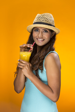 Happy Indian Woman drinking orange juice on a colorful background. Healthy living concept. Young and fresh Asian female model an orange background. photo