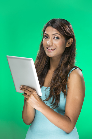 Stylish Indian Woman using a digital tablet PC. Young and fresh Indian female model a bright green background. photo