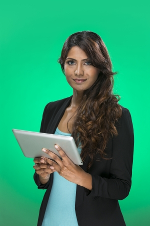 Stylish Indian Woman using a digital tablet PC. Young and fresh Indian female model a bright green background. Stock Photo - 22675000