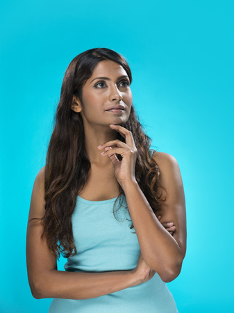 looking upwards: Portrait of happy Indian Woman looking upwards on bright blue background.