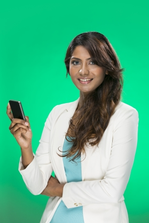 Stylish Indian Woman using a smart phone. Young and fresh Asian female model a bright green background. photo