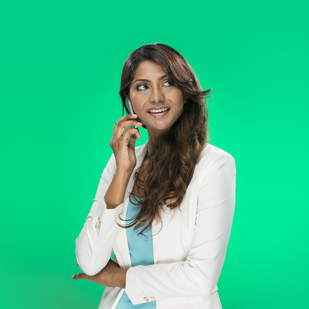 Stylish Indian Woman using a smart phone  Young and fresh Asian female model a bright green background  photo