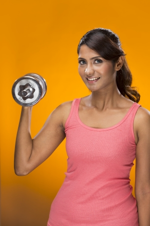 dumbells: Sporty Indian woman exercising with dumb bell weights   On a bright orange background   Stock Photo
