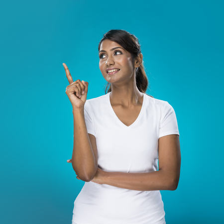 Portrait of happy Indian Woman pointing at something  Young fresh Indian female model on bright blue background   photo