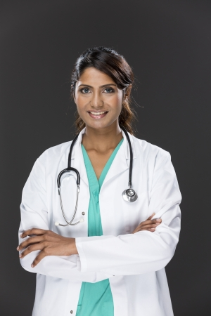 Portrait of a Female Indian doctor wearing a green scrubs  Young and fresh Asian female model a dark grey background