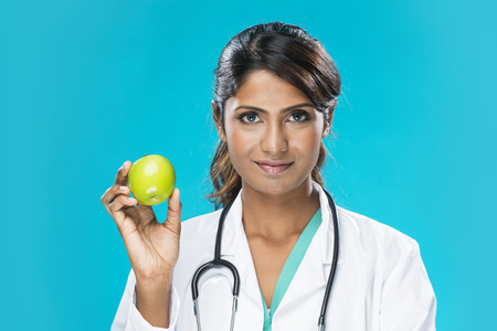Portrait of a Female Indian doctor wearing a green scrubs and holding an apple  Young and fresh Asian female model an blue background  photo