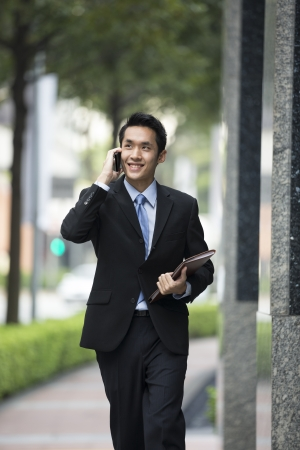 Chinese business Man using his cell phone outdoors in modern Asian city.