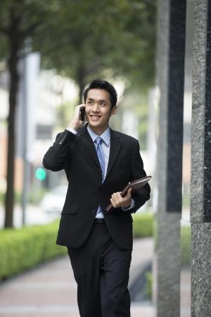 L'homme d'affaires chinois en utilisant son téléphone cellulaire à l'extérieur dans la ville asiatique moderne.