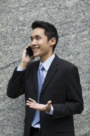 Chinese Business man using a Cell Phone to send a text. Asian Business man texting. Concept about communication.  photo