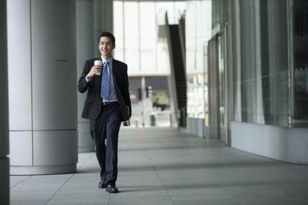 Jeune homme d'affaires asiatique confiant marche dans la ville.