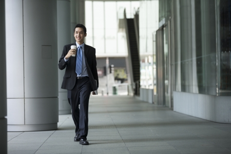 Young confident asian businessman walking in the city. photo