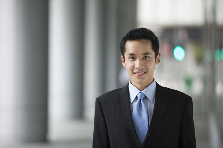 Chinese business man in modern Asian city. Asian businessman smiling & looking at the camera with blurred office buildings as a background. photo