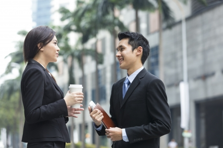 Happy Chinese Business colleagues outside the office talking to each other. Stock Photo